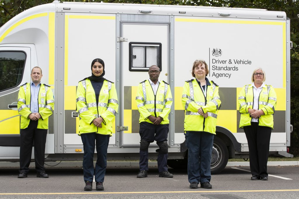A diverse group of DVSA staff in high-visibility jackets and standing in front of a white DVSA van.