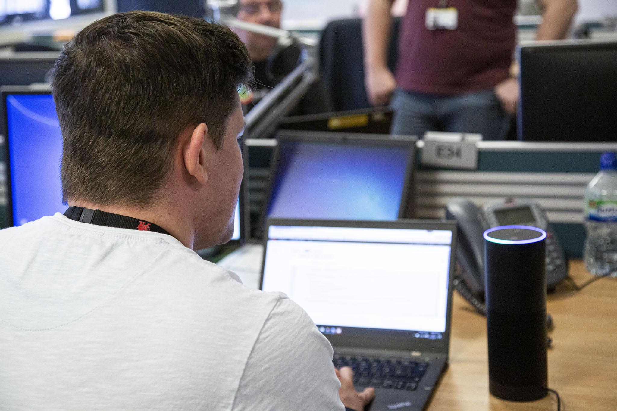 Male DfT Digital professional using a laptop.